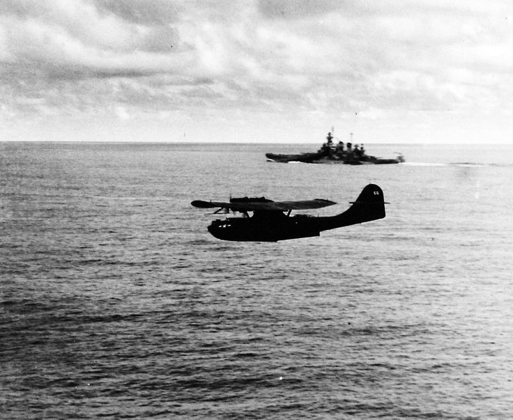 """USS Lexington (CV 16). PBY """"Catalina"""" aircraft flying over a Task Force BB of the North Carolina class, as seen from USS Lexington (CV 16). Photograph released April 25, 1944. Official U.S. Navy photograph, now in the collections of the National Archives."""