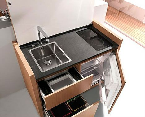 Compact kitchen unit looks like a desk when not in use, but the lid flips up to reveal a sink and two burners. Underneath there's a drawer-style microwave, a small refrigerator/freezer and even a tiny dishwasher.