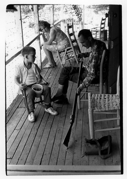 """""""Man cleaning gun on porch as woman and boy watch."""" Eastern Kentucky, 1964. Photo by William Gedney."""