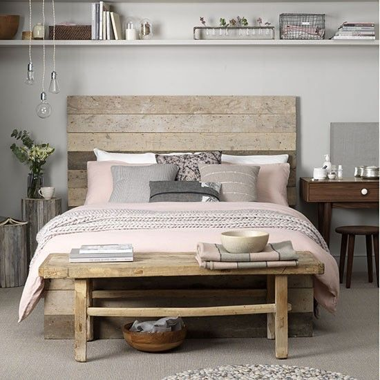 .Natural textures including driftwood night table maple dresser and pink and mauve bedding