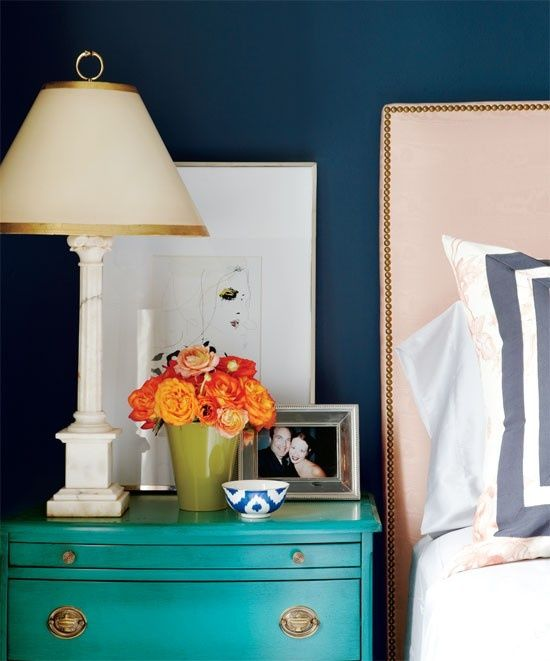 source: Meredith Heron Design Peacock blue walls paint color, turquoise blue chest nightstand, West Elm nailhead Upholstered Headboard, blue Anthropologie ikat bowl, alabaster lamp, olive green vase and art. #blueinterior
