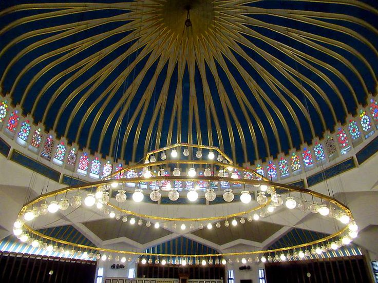 The 168 lanterns on a copper chandelier illuminate the King Abdullah I Mosque in Amman, Jordan. Golden threads point to the 99 Most Beautiful Names of Allah on the neck of the turquoise blue dome.