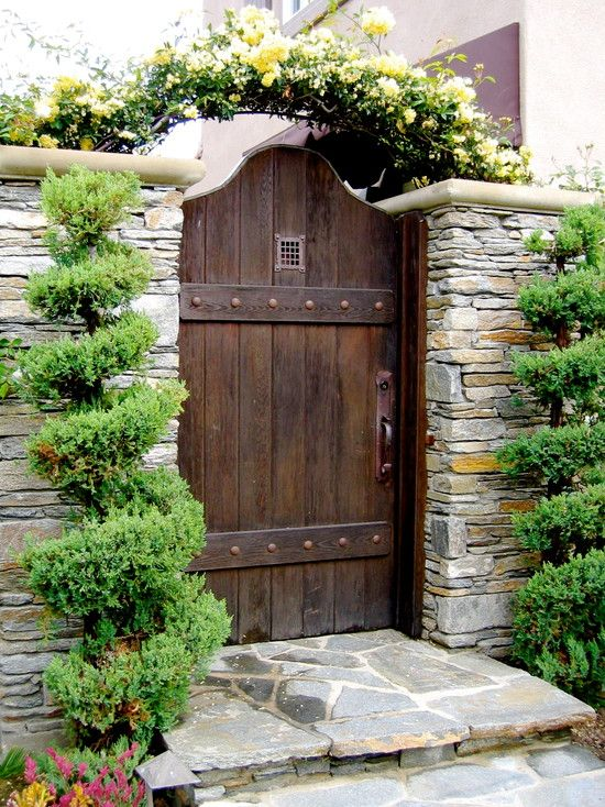 Awesome Wooden Gate Design Ideas with Stone Rock Wall and Wall Plant: Breathtaking Traditional Entry With Wood Gate And Stacked Stone Wall  Plus Handle Iron Gates With Variasion Flower Including Pink And Yellow Flower With Stone Walk Streat And Palm Trees ~ mynines.com Eco-friendly Home Design Inspiration