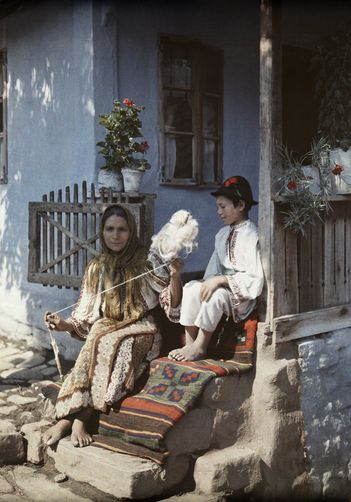 Autochrome: Wilhelm Tobien. A child watches as the woman twists wool to begin making a rug. Romania. 1920s - 1930s.