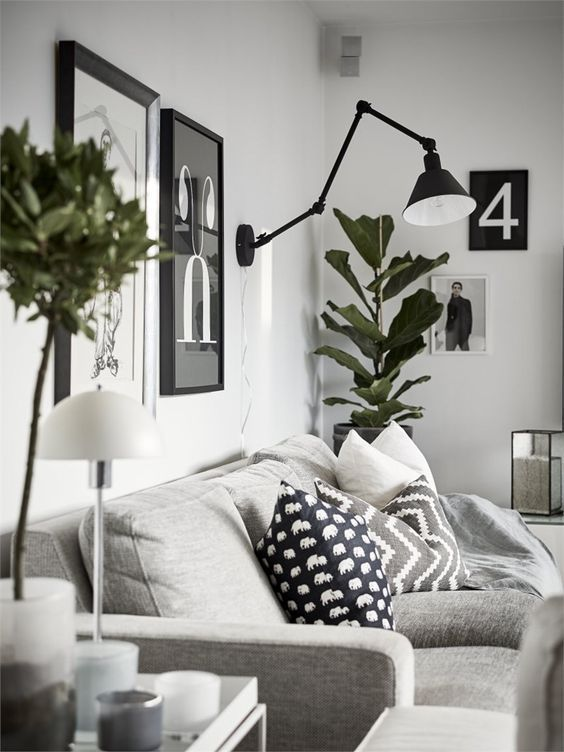 Modern Scandinavian living room with interior in grey, wall art and green plants.