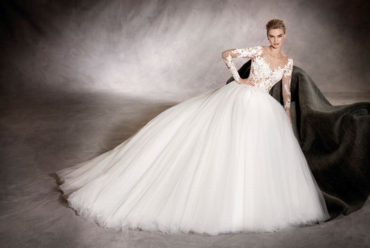 ARLENE - Seduction and romanticism. This long-sleeve princess-cut wedding dress is fitted at the waist that melts into the layers of tulle and lace of the skirt