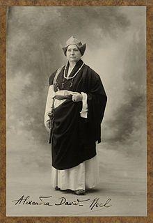 Alexandra David-Néel en costume de lama en 1933. Elle porte un collier fait de 108 rondelles et, sur le côté, un fémur magique[1].