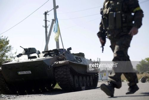 An Ukrainian serviceman walks past an armoured personnel carrier... #karlovka: An Ukrainian serviceman walks past an armoured… #karlovka