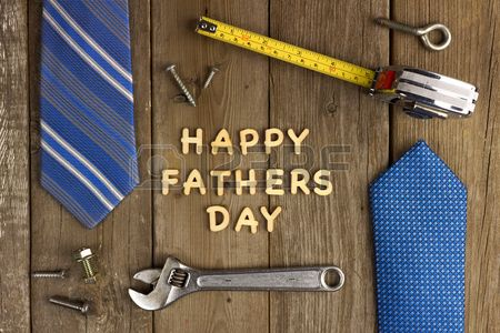 Happy Fathers Day wooden letters on a rustic wood background with tools and ties frame Stock Photo