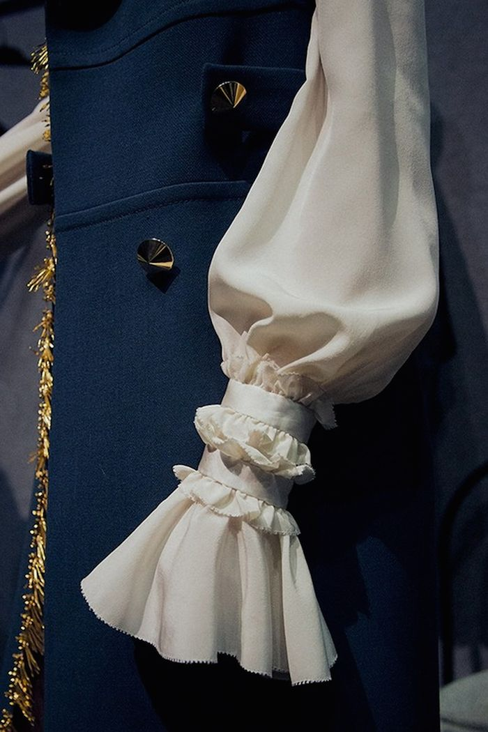 Dark petroleum blue wool with mirror buttons and a white full silk sleeve with ruffles, frills and feminine detailing going in and out, being pulled together and let free to flow by Roberto Cavalli AW15
