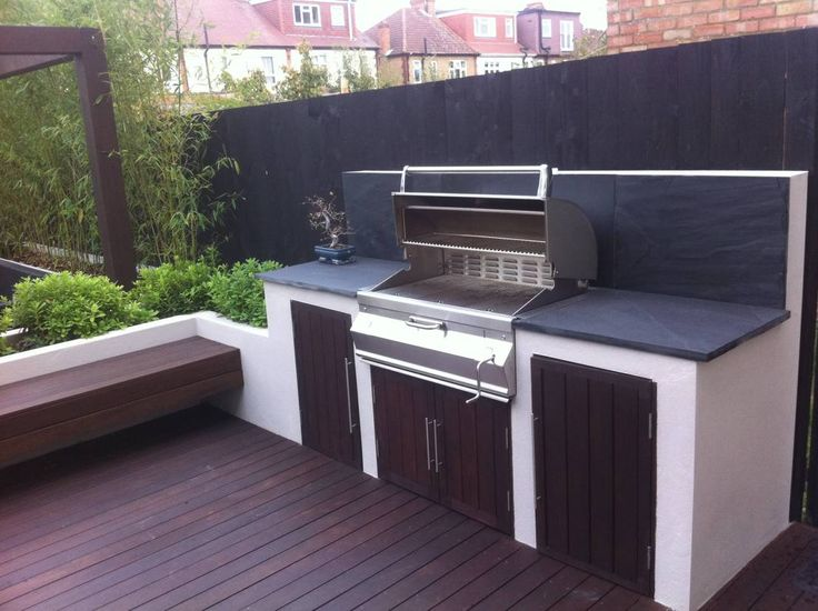 modern garden design with black slate paving, hardwood deck & pergola with floating bench & built in BBQ area. Tall bamboo gives screening & privacy to the boundaries.