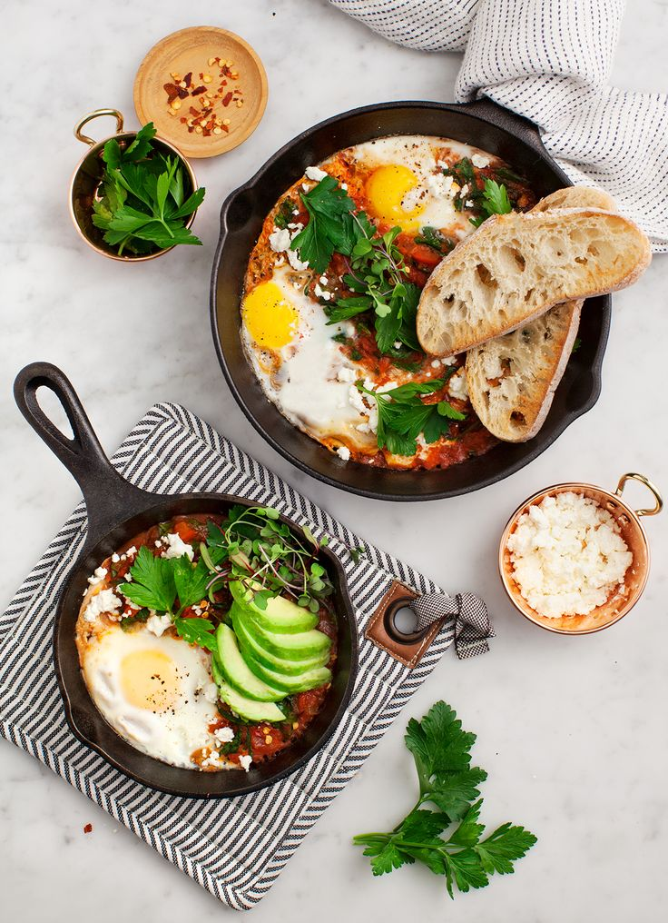 Shakshuka with Spinach and Harissa - A healthy breakfast (or lunch or dinner) of eggs poached in spiced tomato sauce with red peppers and spinach.