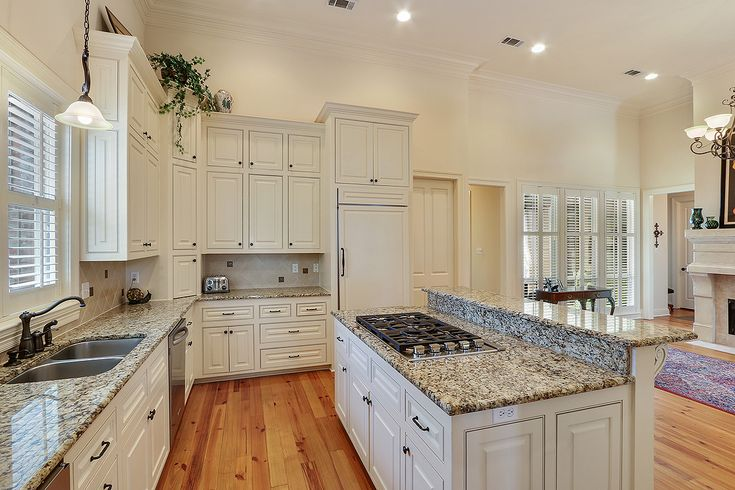 Kitchen is a chef's dream with recently upgraded DCS stainless appliances including high-end built in refrigerator, ice maker, and wine cooler, 3 cm slab granite counter tops, 6 burner gas stove, island with breakfast bar, and towering cabinets.