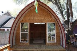 these arched sheds/cabins are relatively cheep and come in a number of sizes.  Some that could fit 2 bedrooms are still under $5000