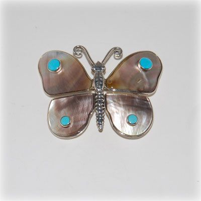 Mother of pearl brooch with turquoise cabochon and handmade sterling silver details and setting. Made in our workshop.
