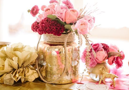 pink roses and red carnations in a gold painted jar