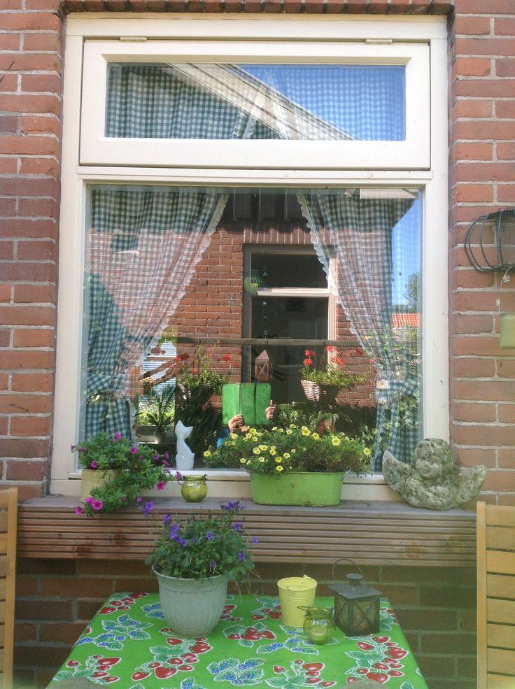 Weerspiegeling van de pergola met geraniums in het raam