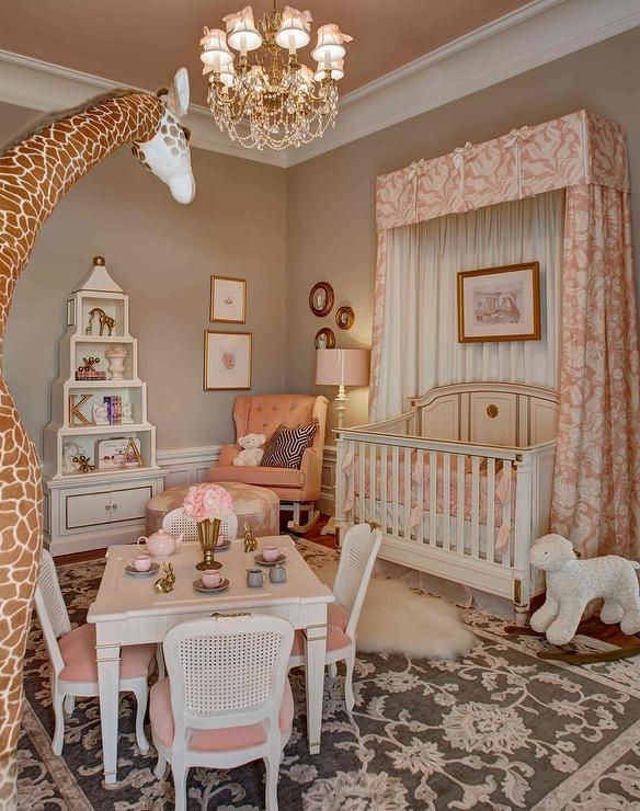 Pin kand taupe nursery features a pink ceiling painted Benjamin Moore East Lake Rose over walls painted Benjamin Moore Smokey Taupe lined with a French crib dressed win Restoration Hardware Baby & Child Washed Appliquéd Fleur Nursery Bedding Collection accented with a pink pleated valance and pink curtains paired with a pink clover ottoman upholstered in Mary McDonald Garden of Persia Fabric atop a cream and brown rug.
