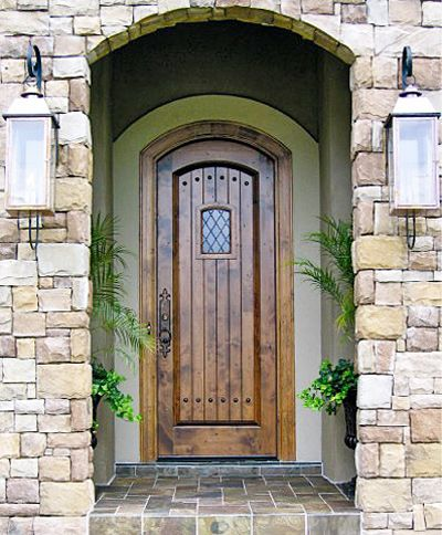 """DbyD-3001 This 36"""" X 96"""" Segment Top V-Groove Raised Panel Door and Jamb was built out of Knotty Alder and was Stained, Finished and Installed in Montgomery, Alabama.  We used 8711 Casing with 8387 Backband for Interior and Exterior Casing.  The Hardware is Rocky Mountain in White Bronze Dark Finish and 12 matching Clavos.  The door was stained with Highlighted Special Cherry Stain. The glass is Leaded Seedy Diamonds and there is a Speak Easy Door on the Inside."""