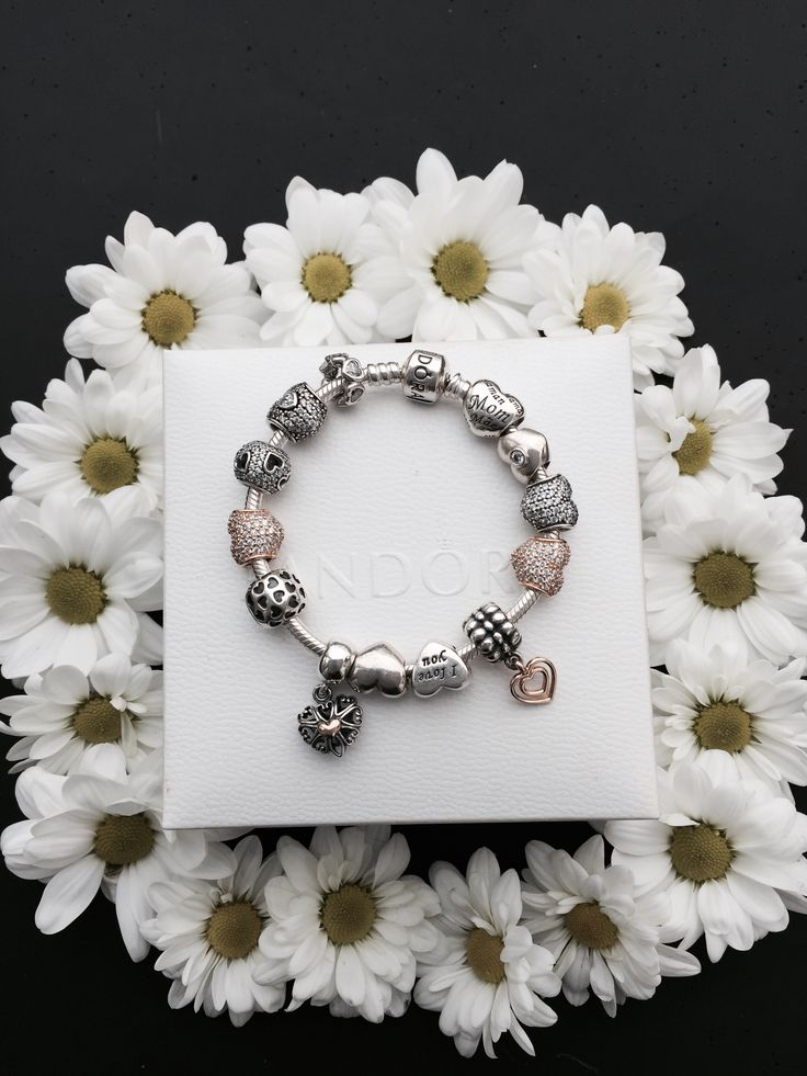 Flowers and hearts are always a great combination. Lovely white daisies surrounding a beautiful PANDORA bracelet with sterling silver and 14k gold heart charms. #PANDORA #PANDORAbracelet