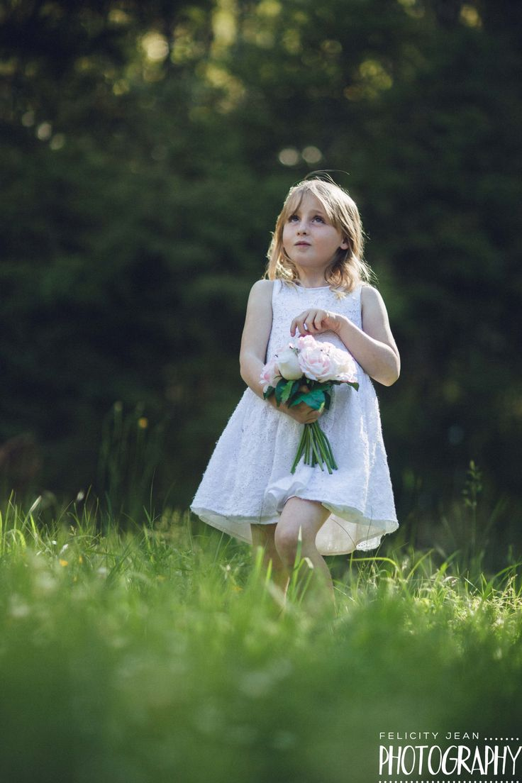 posing for a photo dresses as a flower girl on her mum's wedding day by felicity jean photography