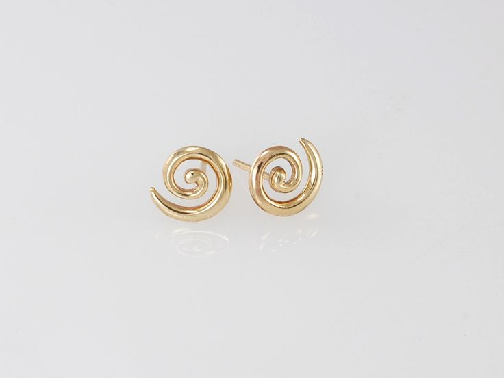 """Gold Koru Stud Earrings. NZ$299 9ct yellow gold. These simple studs will become your everyday """"go to"""" favorites. Also available in in silver or with diamon centres.  The koru (spiral) represents the unraveling of the silver fern frond as it opens bringing new life and purity to the world. Symbolizing peace, tranquility and spirituality along with a strong sense of regrowth or new beginnings.  Jewellery made @jewelbeetle in Nelson, New Zealand"""