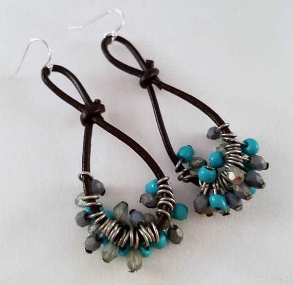 A dangle made of leather cord holds 24 small turquoise and clear beads which are attached with silver head pins. The earrings hang approximately 3 inches in length and have a sterling silver earring wire.
