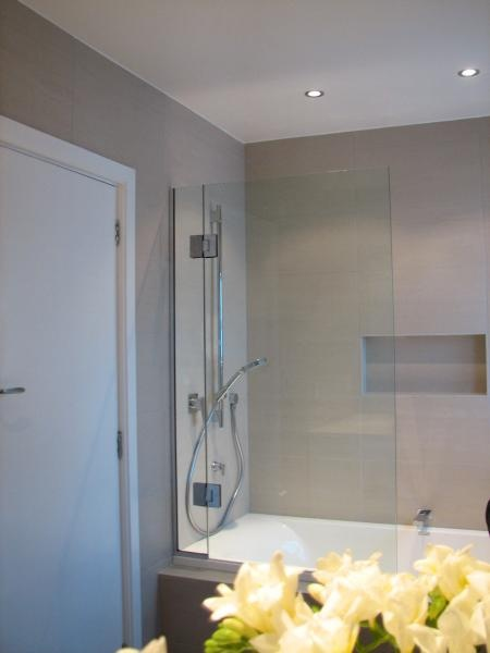 Shower over bath with recessed shelf.