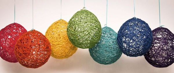 Dip colored yarn in watered down glue, wrap around inflated balloon, wait for it to dry, then pop ballon
