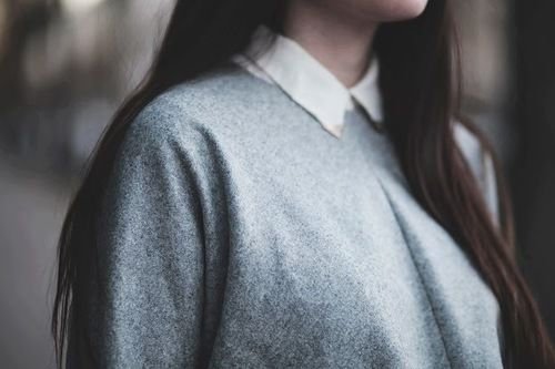 ash grey jumper and white collar.