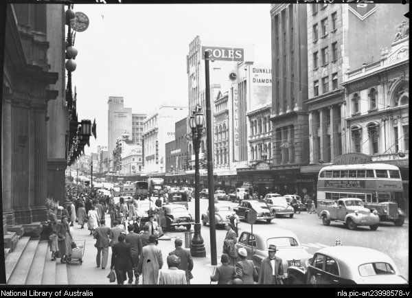 Hurley, Frank, 1885-1962. Bourke Street, Melbourne [Coles, Dunklings, the Odeon, the Tivoli, the Royal Arcade and a double-decker bus with the slogan Serve to save Australia] [picture] : [Melbourne, Victoria]