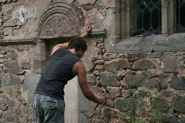 Raking out crumbling lime mortar from the joints, and replacing with soft hydraulic lime mortar to allow the building to breathe and stay dry.