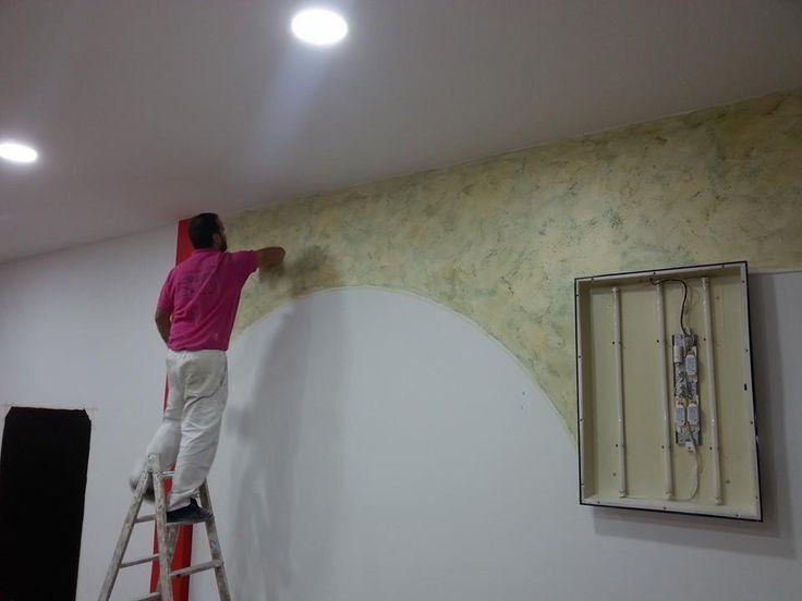 Decorando con estuco en una de las paredes de un local de - Materiales para insonorizar paredes ...