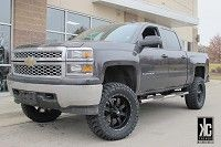 Red Dirt Road RD01 Dirt matte black wheels mounted  with AMP M/T tires and a 7.5 inch RCX Lift kit on a  Silverado.