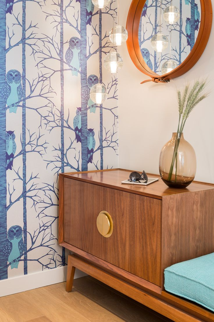 Entry - Calming blue Owl Wallpaper with glass pendant, leather mirror and teak chest with upholstered seat. #CamillaMeijer #Bocci #Gubi #JonathanAdler