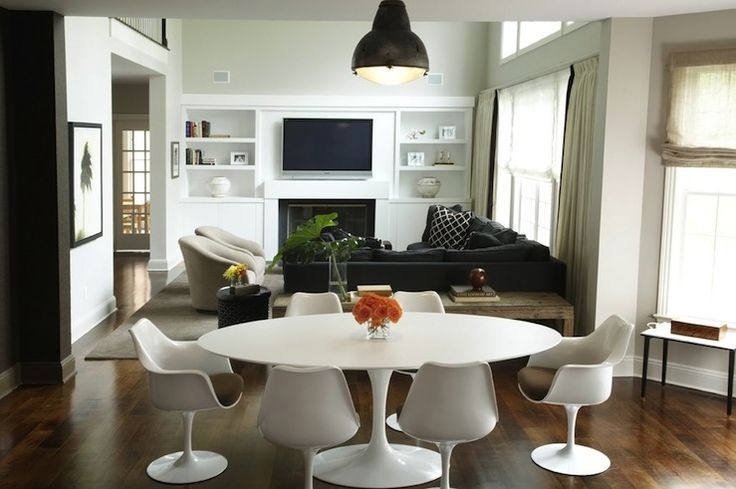 Modern dining room design with oval Saarinen Table, Saarinen Tulip Chairs, charcoal gray sectional sofa, tv and built-ins.