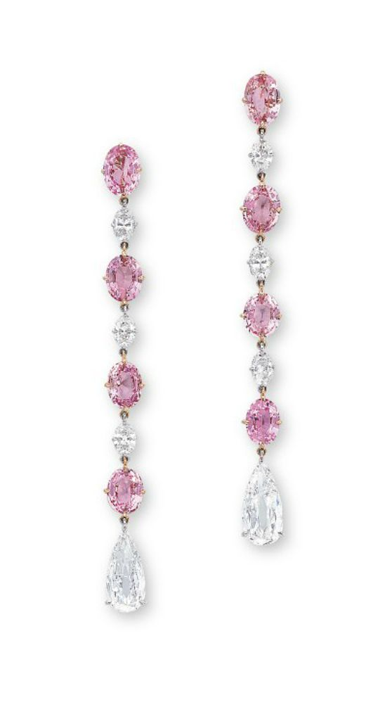A PAIR OF PADPARADSCHA SAPPHIRE AND DIAMOND EAR PENDANTS. Each set with a line of oval-shaped padparadscha sapphires weighing approximately 1.58 to 1.26 carats, alternating with oval-shaped diamonds, terminating in pear-shaped diamonds, mounted in 18k rose and white gold.