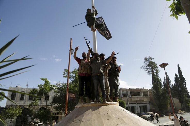 A member of al Qaeda's Nusra Front climbs on a pole to hang the Nusra flag as others celebrate around a central square in Ariha, May 29, 2015. Images seen by Reuters from inside Ariha on Friday showed a fighter climbing a flagpole to raise a Nusra Front flag in the town's central square as fighters cheered below him. Another showed men with guns sitting on a pavement. REUTERS/Khalil Ashawi