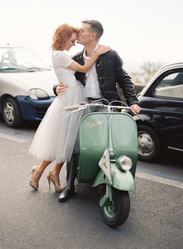 Philip kisses Rae durring wedding engagement photos on vintage vespa in Positano, Italy