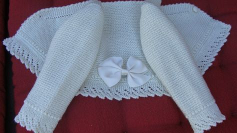 "Beautiful baby jacket with lace trimming and grosgrain ribbon on the back. For this type of basic jacket (shortish, V-neck), you can follow the detailed instructions in the blog ""Liando Labores de Punto"" [http://liandolaborespunto.blogspot.com/2013/11/chaquetita-basica-bebe.html] by Emilia Alvarez Perdiguero. The lace edging is very easy to add."
