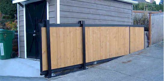 Sliding gate over driveway doubles as a fence urban for Sliding driveway gate hardware