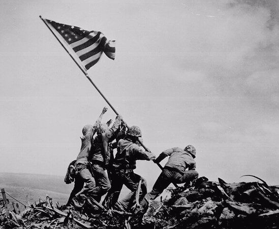 Five Marines and a Navy hospital corpsman raise the flag on Mount Suribachi, Iwo Jima, using a piece of Japanese pipe as a mast, February 23, 1945. The flag raising photo and subsequent statue came to symbolize being a Marine.