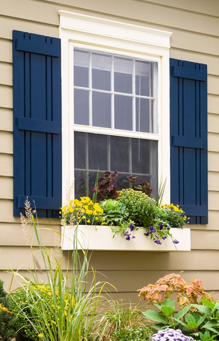 Dark blue shutters on a beige house. Flank a window with decorative outdoor  shutters you can make yourself and paint for maximum impact.