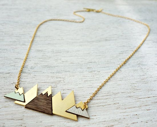 A signature necklace with an urban chic statement, inspired by Scandinavian design. Geometric triangular mountain shapes create a bold pendant, hanging from a chain. Made of high quality 24K matte gol