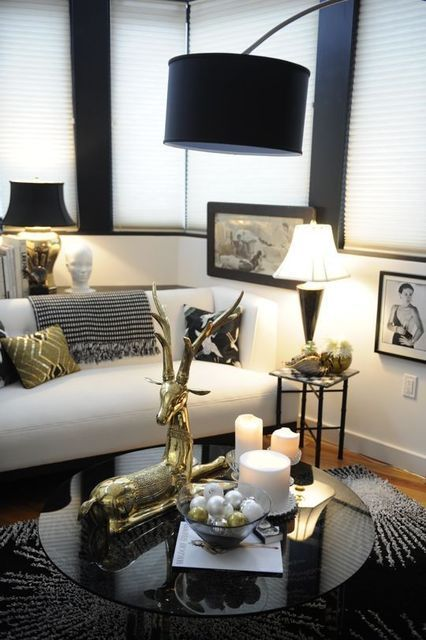 This living space features a black white palette with gold accents. I love the modern feel that deer on the coffee table is delightful. Note the art hung low on the wall. Know the rules when to break them....V