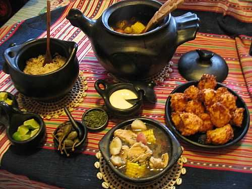 Ajiaco (Colombian potato, avocado, corn soup) along with garnishes, rice and cheese fritters
