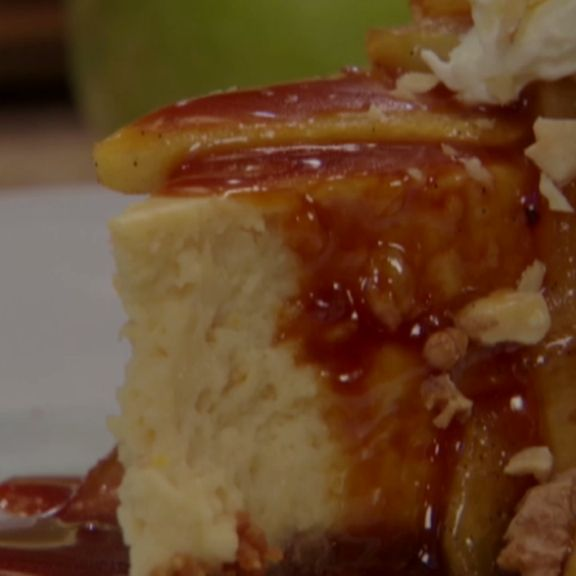 Bobby Flay tops cheesecake with sauteed apples, homemade apple-caramel sauce and a sprinkle of walnuts.
