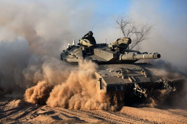 A soldier sits on top of a Merkava tank, part of the Israeli army deployment near Israel's border with the Gaza Strip. Photograph: Menahem Kahana/AFP/Getty Images