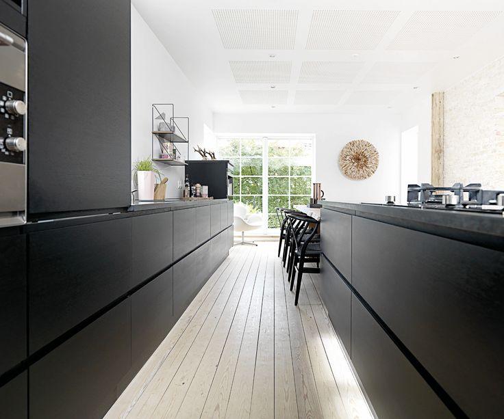Køkkenet i sort eg giver en rå og maskulin kontrast til den rå murstensvæg og de flotte gamle gulvplanker, der dukkede frem, da linoleumsgulvet blev fjernet. Se mere på www.jke-design.dk.