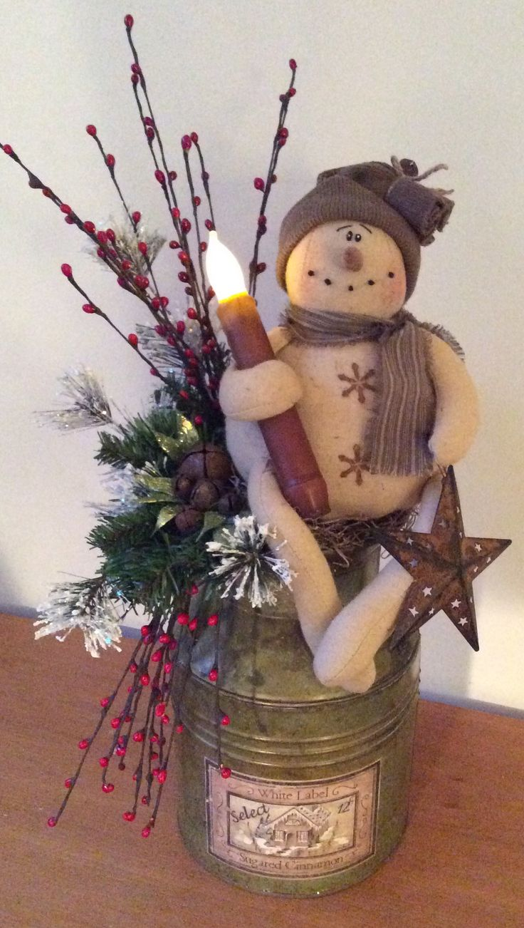 """Reproduction vintage milk can - this little frosty guy holds a perforated, rusty star and a battery operated, wax dipped flicker candle. Embellished with pine, frosted Ming, glittery leaves, assorted rusty jingle bells and berry sprigs. The vintage label on the milk can read, """"White Label Sugared Cinnamon"""". This is a one of a kind piece. $29"""